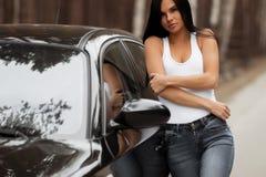 Девушка брюнета положенная против автомобиля стоковое изображение rf