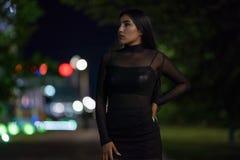 Девушка брюнета представляет против выравниваясь города ночи, красочные света освещает ходя по магазинам окна стоковая фотография rf
