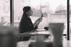 Девушка брюнет азиатская используя smartphone в кафе, черно-белом стоковые изображения rf