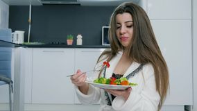 Девушка брюнет в белом купальном халате с плитой салата и вилка в руках закрывают вверх на кухне предпосылки сток-видео