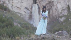 Девушка брюнет в платье на предпосылке водопада видеоматериал