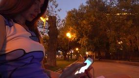 Девушка брюнет в платье с красным маникюром используя ее smartphone на улице вечера видео 4K сток-видео