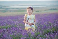 Девушка брюнет в соломенной шляпе держа корзину с лавандой Девушка брюнет с 2 оплетками в поле лаванды Милая девушка внутри Стоковая Фотография