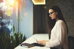 Девушка брюнет в стеклах выполняет ежедневное содержание работы через портативный ПК соединенный к беспроволочному интернету в ко Стоковое Фото