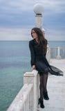 Девушка брюнет в черном платье представляя на пристани Стоковые Фото