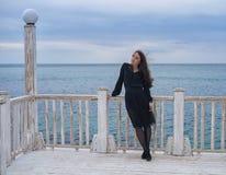 Девушка брюнет в черном платье представляя на пристани Стоковые Фотографии RF