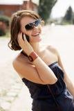 Девушка брюнет говорит телефоном и смеется над стоковое фото