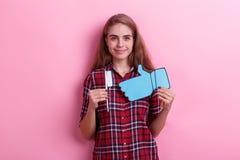 Девушка, брюнет держа зубную щетку белой бумаги и голубой знак обратной связи и милой улыбки стоковое фото