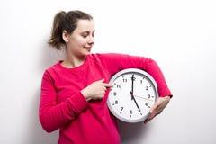 Девушка брюнет держит часы и пункты к рукам часов на w Стоковые Фотографии RF
