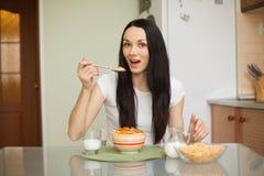 Девушка брюнет есть завтрак с молоком стоковое фото rf