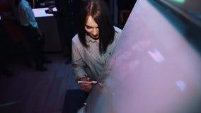 Девушка брюнет играя игра-угадайку чертежа на событии торжества в баре сток-видео