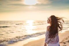 Девушка брюнет на предпосылке захода солнца моря Стоковые Изображения
