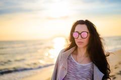 Девушка брюнет на предпосылке захода солнца моря Стоковое Изображение RF