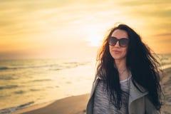 Девушка брюнет на предпосылке захода солнца моря Стоковое Изображение