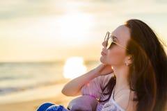 Девушка брюнет на предпосылке захода солнца моря Стоковая Фотография