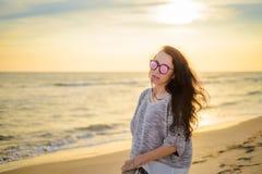 Девушка брюнет на предпосылке захода солнца моря Стоковое фото RF