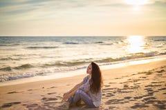 Девушка брюнет на предпосылке захода солнца моря Стоковые Изображения RF
