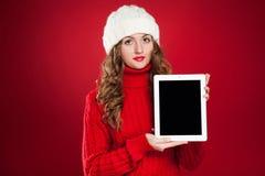 Девушка брюнет нося красный свитер и держа таблетку стоковые изображения