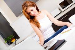 Девушка брюнет работая в кухне стоковые изображения