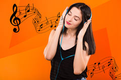 Девушка брюнет с голубыми наушниками и с музыкальными примечаниями Стоковое Изображение RF