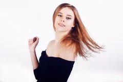 Девушка брюнет с длинными и сияющими волосами Красивая модель с стилем причёсок, танцем Довольно красивая девушка на белой предпо Стоковое Фото