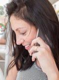 Девушка брюнет с striped беседой футболки на сотовом телефоне Стоковое Изображение