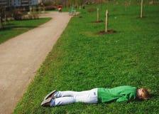 Девушка была утомлена и лежала вниз для того чтобы ослабить на траве около дороги Стоковое фото RF