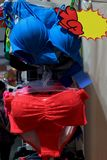 Девушка бюстгальтера, нижнего белья красная и голубая моды, магазин женское бельё на рынке ночи улицы Стоковые Фотографии RF