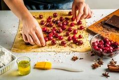 Девушка варит штрудель с шоколадом и вишнями Стоковая Фотография