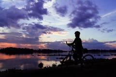 Девушка велосипеда силуэта на заходе солнца Стоковые Фотографии RF
