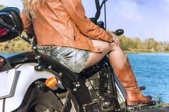 Девушка велосипедиста в кожаной куртке на мотоцикле около реки Стоковые Изображения RF