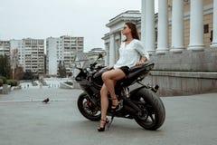 Девушка велосипедиста едет мотоцикл в дожде взгляд Перв-персоны стоковое изображение rf