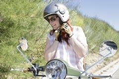 Девушка велосипедиста пробуя на шлеме мотоцикла Стоковые Фотографии RF