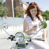 Девушка велосипедиста смотря ее мобильный телефон Стоковое фото RF