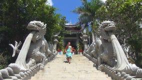 Девушка взбирается вверх лестницы лестница украшенная с статуями драконов сток-видео