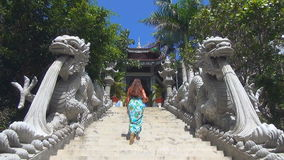 Девушка взбирается вверх лестницы лестница украшенная с статуями драконов акции видеоматериалы
