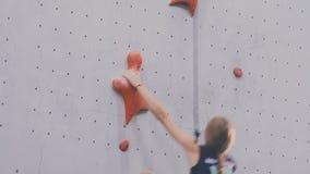Девушка взбирается вверх на стене тренировки видеоматериал