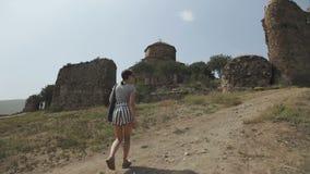 Девушка взбирается вверх холм к старой каменной церков на верхней части горы скит jvari Georgia видеоматериал