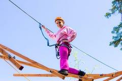 Девушка взбирается в веревочки курс стоковая фотография rf