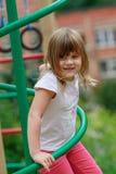 Девушка взбирается лестницы на спортивной площадке Стоковые Фото