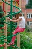 Девушка взбирается лестницы на спортивной площадке Стоковое фото RF