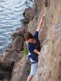 Девушка взбираясь вверх скала Стоковая Фотография RF