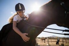 Девушка взбираясь задняя часть лошади в ранчо Стоковая Фотография RF