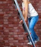 Девушка взбираясь лестницы к верхней части стоковые фото