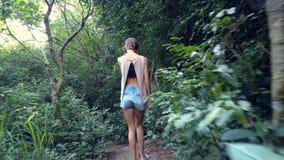 Девушка взгляда задней стороны идет вниз с каменных шагов в джунгли сток-видео