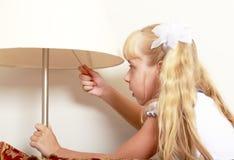 Девушка включает лампу пола Стоковые Изображения RF