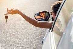 Девушка водителя держит ключи к вашему автомобилю Стоковая Фотография RF