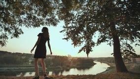 Девушка восторженно бежит для встречи захода солнца на предпосылке города и поднимает ее руки Видео в движении акции видеоматериалы