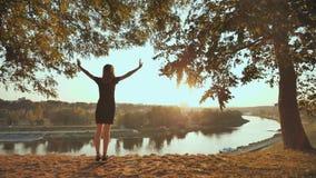 Девушка восторженно бежит для встречи захода солнца на предпосылке города и поднимает ее руки Видео в движении видеоматериал