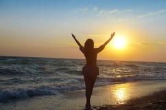 Девушка восхищая заход солнца на береге моря Стоковая Фотография RF